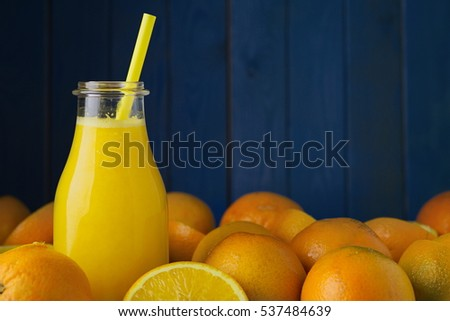 Freshly squeezed organic orange juice in bottle with colored straw and ripe organic oranges oranges against blue wood boards background. Selective focus on straw. Concept of health Concept of detox