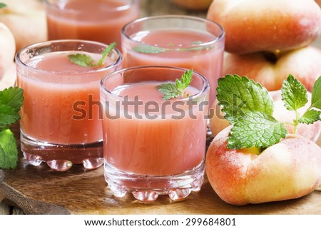 Freshly squeezed pink peach juice in glasses, selective focus