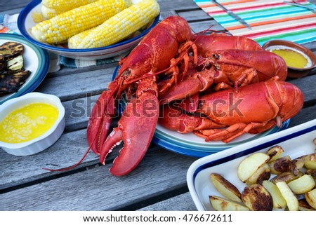 Freshly steamed whole Maine lobsters on plate with butter sauce, and vegetables. Selective focus on front part of lobsters.