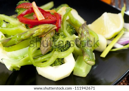 Freshly stir fried Thai  green salad with asparagus tips, cucumber, broccoli, green and red pepper, chili with a fish sauce, vinegar and brown sugar dressing.  On a black plate. - stock photo
