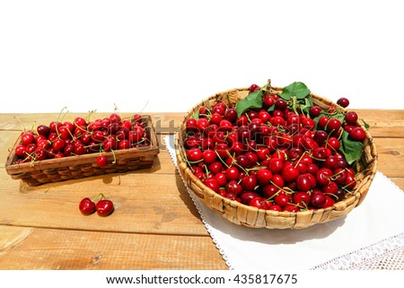 Freshly sweet cherries in a wicker baskets on the wood. Rustic style. Sunny day. White background as a copy space  - stock photo
