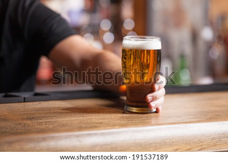 Freshly tapped beer. Bartender holding a freshly tapped glass of beer in his hand - stock photo