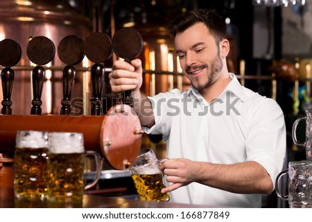 Freshly tapped beer. Cheerful young bartender pouring beer and smiling - stock photo