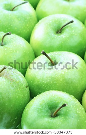 Freshly washed green apples lined up neatly. Selective focus on second apple from the bottom. - stock photo
