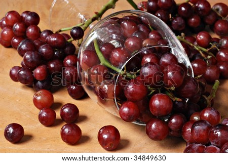 Freshly washed red grapes spilling from crystal wine glass onto wood table.  Macro with shallow dof. - stock photo