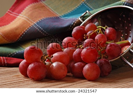 Freshly washed red grapes spilling from metal colander.  Colorful table linen as background.  Macro with extremely shallow dof. - stock photo