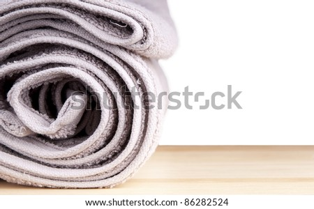 Freshly washed rolled towels isolated on white - stock photo