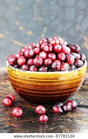 Freshly washed whole cranberries against a rustic background with selective focus.  Room for copy space. - stock photo