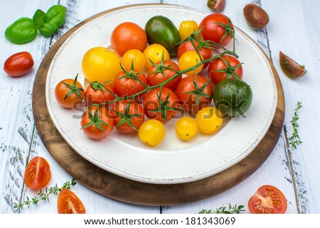 Freshly washed yellow, red, green and black tomatoes on a vintage plate on a white painted shabby wooden surface