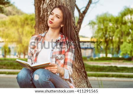 Freshness and summer relaxation concept with young hipster standing next to a tree and reading a book outside - stock photo