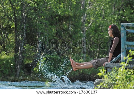 Freshness! Girl playing with river splashes. - stock photo