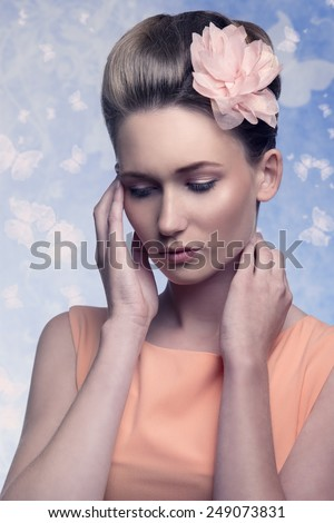 freshness young woman in lovely pose with flower in the elegant hair-style and orange dress. beauty close-up portrait, skin-care  - stock photo