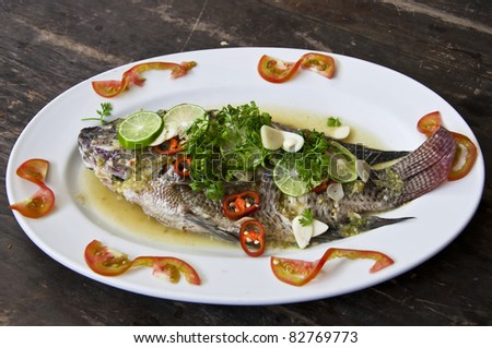 Freshwater fish steamed with lemon and sauce. - stock photo