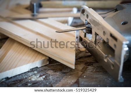 Fretsaw, hammer, knife and tongue and groove boards on working place, closeup