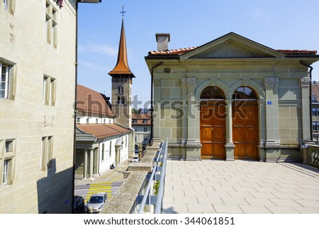 FRIBOURG, SWITZERLAND - SEPTEMBER 10, 2015: Urban scene with visible tower of the Basilica of Our Lady (Basilique de Notre-Dame) in the capital city of the canton of Fribourg - stock photo
