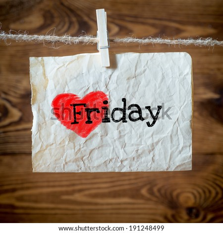 Friday on red heart on aged paper hanging on the clothesline. On old wood background - stock photo
