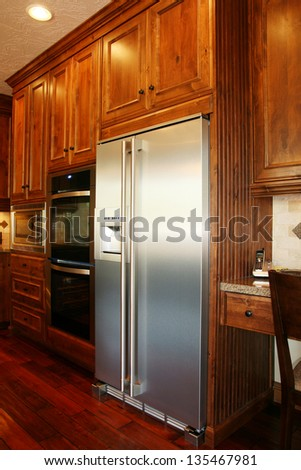 fridge and stacked wall ovens in kitchen