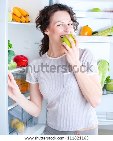 Fridge. Healthy Eating Concept .Diet. Beautiful Young Woman near the Refrigerator with healthy food. Fresh Fruits and Vegetables
