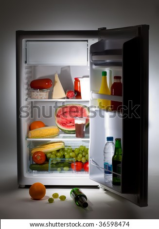Fridge with open door and food on the floor - stock photo