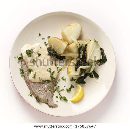 Fried and peppered escalope of veal served with  potatoes mixed with wilted chard and a creamy gravy, all garnished with chopped herbs and served with a lemon wedge, from above - stock photo