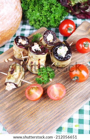 Fried aubergine with cottage cheese, parsley and bread on wooden background