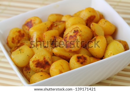 Fried baby potatoes with spices, close up  - stock photo