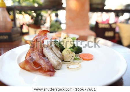 fried bacon and sausages with vegetables