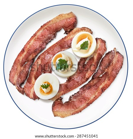 Fried Bacon Rashers with three hard boiled Egg slices with Mayonnaise and Parsley Leaves, on Porcelain Plate, Isolated on White Background. - stock photo