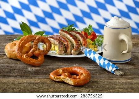 Fried Bavarian sausages on potato salad served with pretzels and half a liter of Bavarian beer in a tankard, in the background the white-blue flag of Bavaria - stock photo
