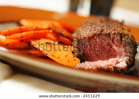 Fried beef steak with carrots on the side - stock photo