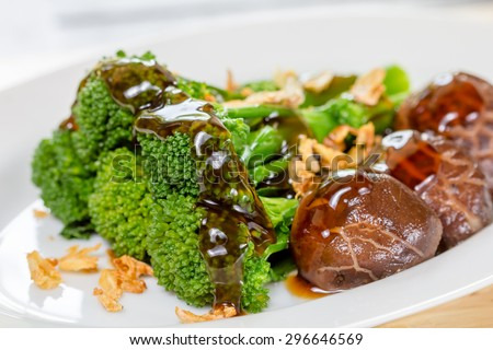 Fried Broccoli With mushroom sauce, oyster sauce on a white plate in a restaurant - stock photo