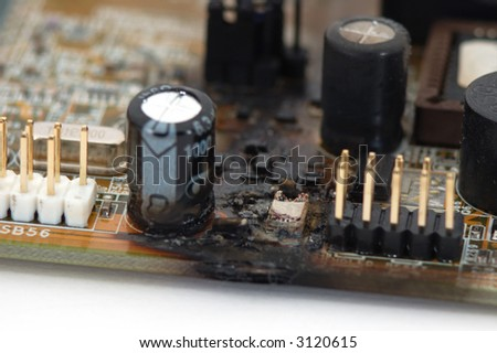 Fried (burnt) computer motherboard, with exploded chip.