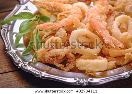 Fried calamari and shrimps on wooden table  - stock photo