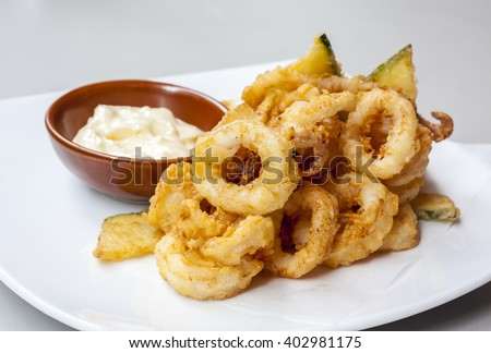 fried calamari rings on whaite plate with dipping sauce  - halal food, selective focus. - stock photo