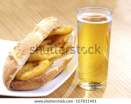 Fried Calamari. Spanish Tapa. �Tapas� are typical spanish appetizer. One of them: �Calamares a la romana�,  batter-coated squid rings deep fried, and served with lemon on the side, or  as a sandwich. - stock photo