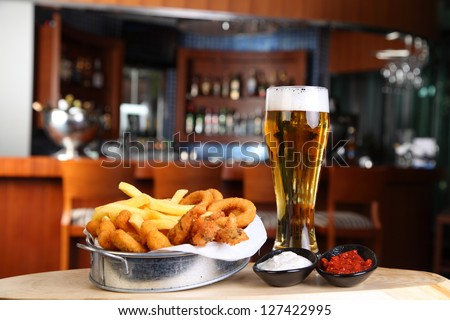 Fried calamari with a glass of beer in pub - stock photo