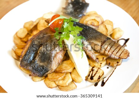 Fried carp fillet with fried potatoes - stock photo