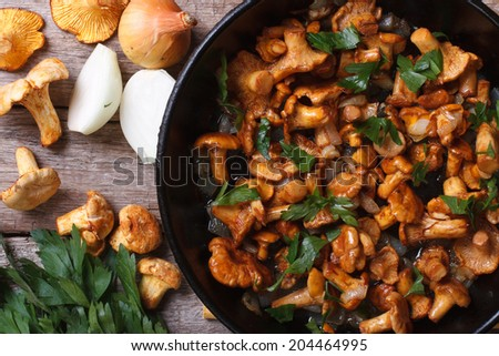 fried chanterelle mushrooms with onion and parsley in a frying pan and ...