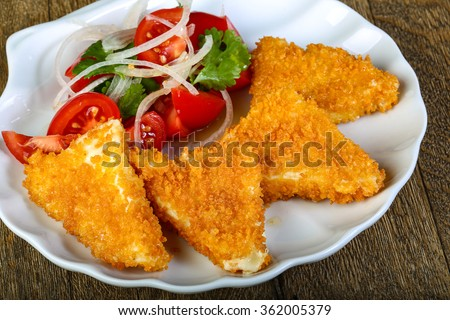 Fried cheese triangles with vegetables salad - stock photo