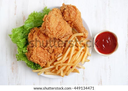 fried chicken and french fries on a wooden background - stock photo