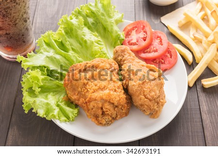 Fried chicken and french fries on a wooden table. - stock photo