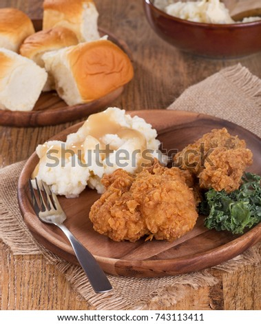 Fried chicken and mashed potatoes with dinner rolls on wooden plates