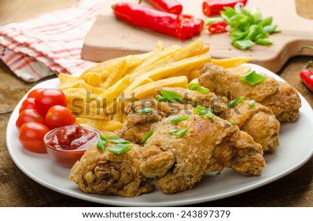 Fried chicken, chilli fries and dip and spring onions on top of meal - stock photo