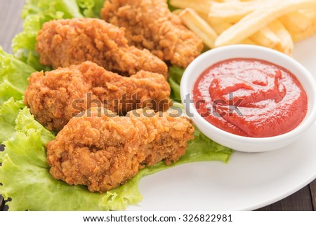 fried chicken drumstick and french fries on white dish. - stock photo