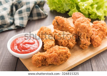 fried chicken drumstick and vegetables on wooden background. - stock photo