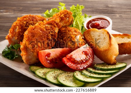 Fried chicken drumsticks and vegetables - stock photo