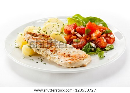 Fried chicken fillet, boiled potatoes and vegetables - stock photo