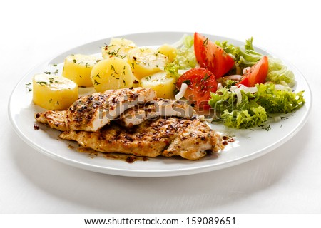 Fried chicken fillets, boiled potatoes and vegetables - stock photo