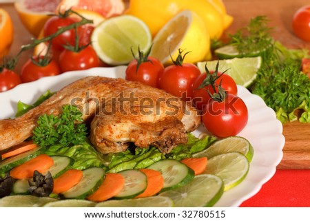 Fried chicken leg with lemon and cucumber on a plate
