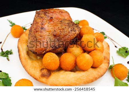 Fried chicken leg with potato balls on the cake with parsley and dill in a bowl - stock photo